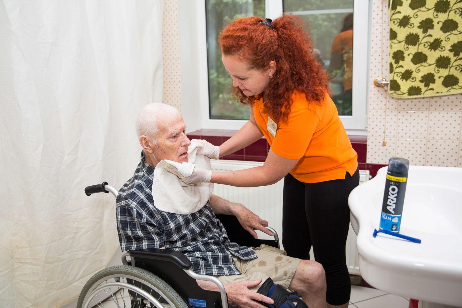 Сотрудница бреет лицо мужчине в инвалидной каляске