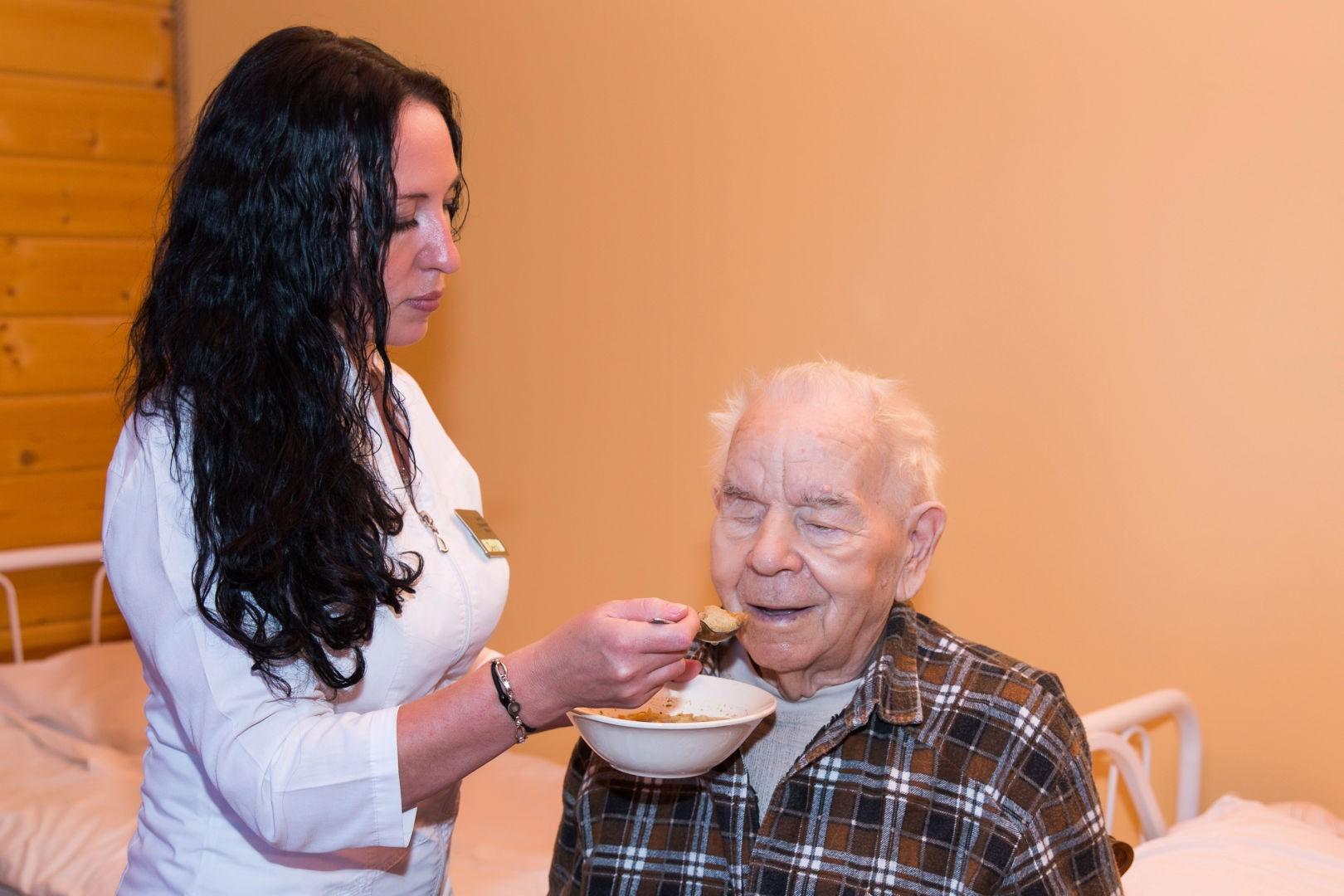 Сиделка кормит дедушку
