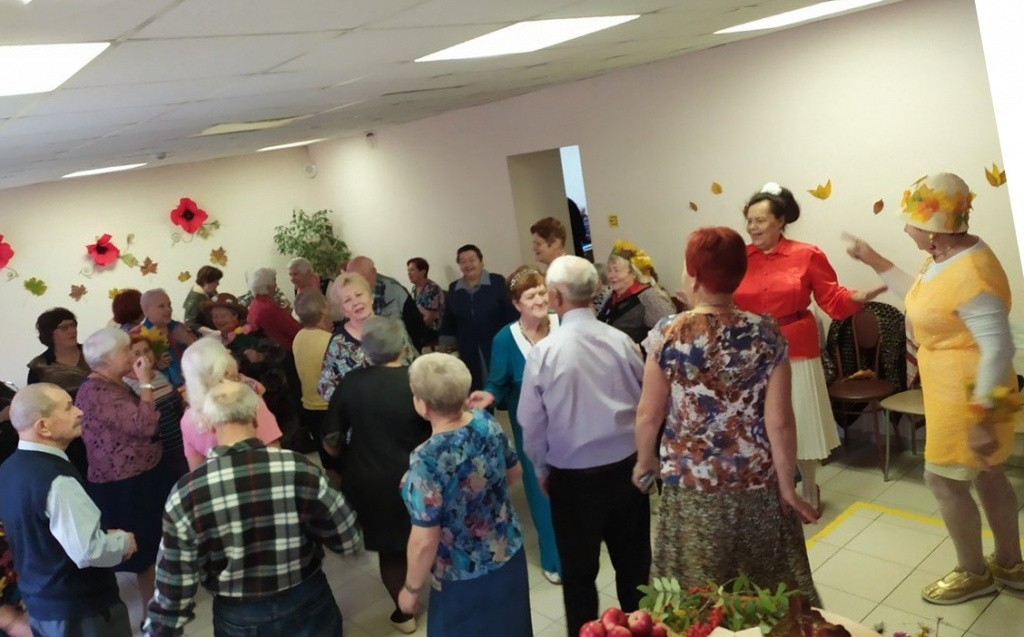 пожилые люди стоят в комнате