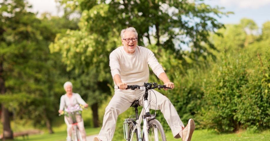 мужчина едет на велосипеде по парку золотой осенью