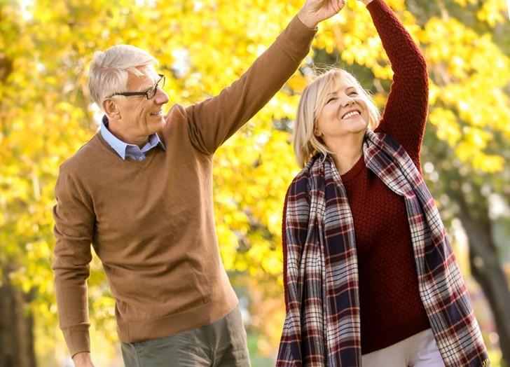 дедушка и бабушка гуляют в сквере осенью