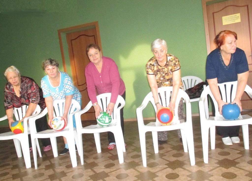 бабушки играют в игру со стульями и мячами