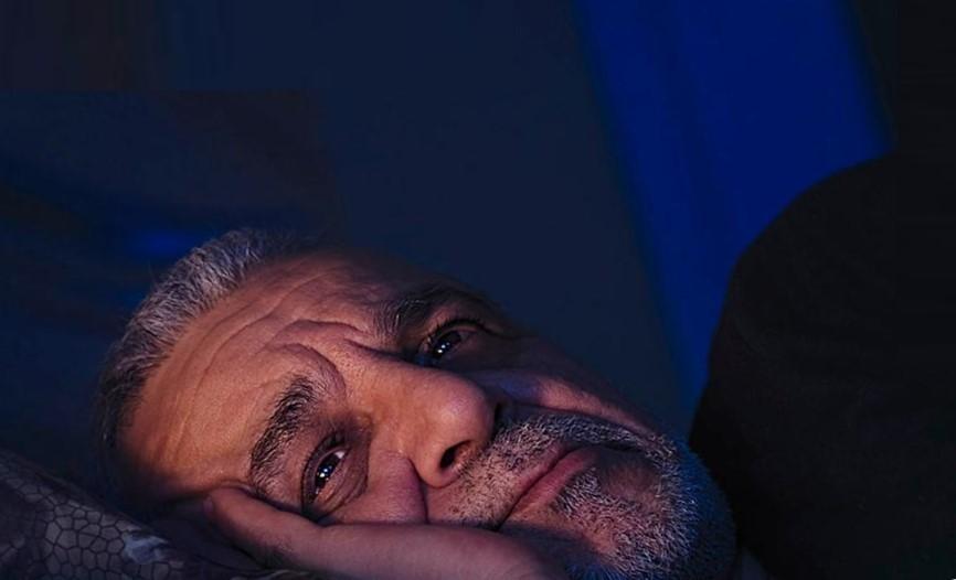 мужчина лежит в спальне, подпирает голову ладонью, на лицо падает свет от лампы