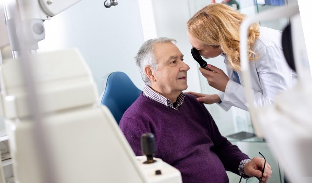 доктор проверяет зрение у дедушки