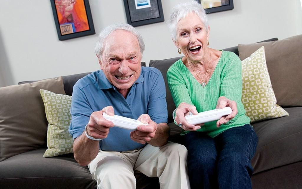 бабушка и дедушка сидят на диване в светлой комнате и играют в приставку